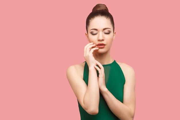 Ritratto di bellezza di bella giovane donna seria calma con l'acconciatura e il trucco del panino in abito verde in piedi, con gli occhi chiusi e toccandole il viso. foto in studio al coperto, isolata su sfondo rosa