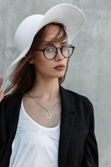 Ritratto di bellezza ragazza carina con belle labbra in occhiali alla moda in eleganti vestiti bianchi e neri e cappello vintage estivo su sfondo grigio vintage all'aperto.