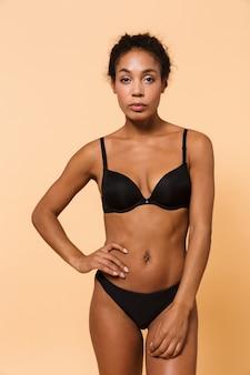 Ritratto di bellezza della donna elegante che indossa lingerie nera, in piedi isolato sul muro beige