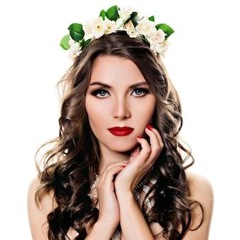 Ritratto di bellezza di una ragazza con lunghi capelli ricci e corona di fiori sulla testa su sfondo bianco
