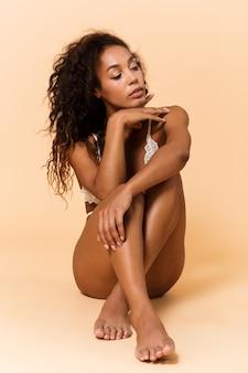 Ritratto di bellezza della donna glamour che indossa lingerie bianca, seduta sul pavimento isolato sopra il muro beige