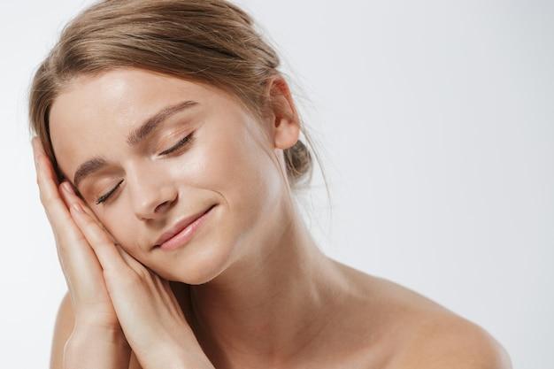 Ritratto di bellezza di una splendida giovane donna bionda seminuda con i capelli legati che dorme alle sue mani isolate su bianco