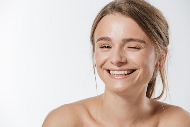 Ritratto di bellezza di una splendida giovane donna bionda seminuda con i capelli legati che strizzano l'occhio alla telecamera isolata su bianco