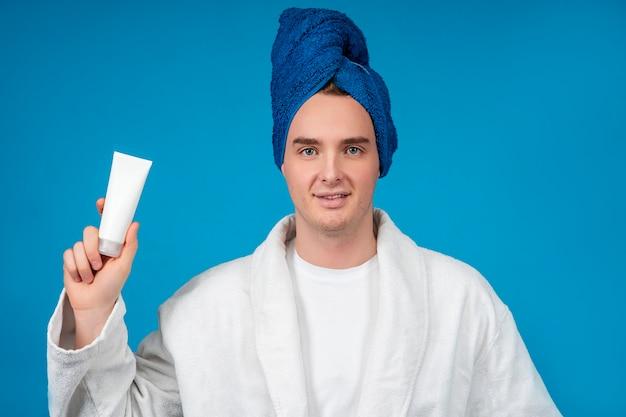 Ritratto di bellezza di bel ragazzo bello, giovane uomo in asciugamano, accappatoio con pelle chiara che tiene