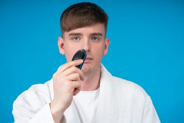 Ritratto di bellezza del bel ragazzo giovane in accappatoio bianco utilizzando un rasoio elettrico o un rasoio a