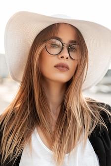 Ritratto di bellezza bella giovane donna con pelle pulita tenera con capelli castani con labbra sexy in occhiali di moda in top bianco in cappello di paglia in blazer nero giovanile in giornata di sole luminoso all'aperto. signora elegante.