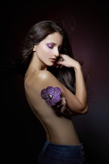 Ritratto di bellezza di una donna nuda con un fiore viola tra le mani su uno sfondo scuro. cosmetici naturali, trucco naturale