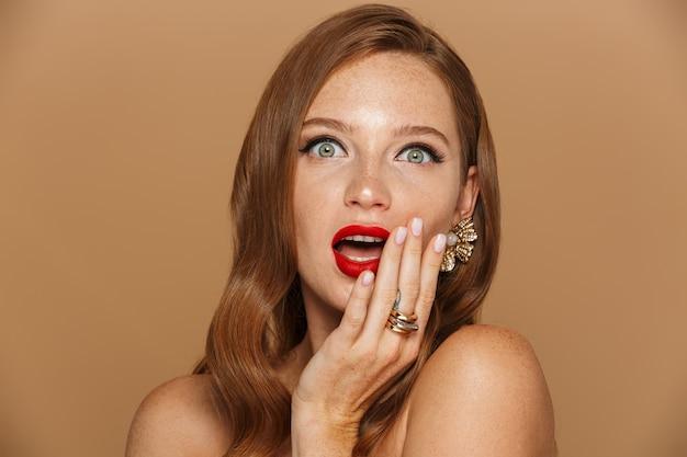 Ritratto di bellezza di una donna abbastanza giovane con capelli rossi lunghi che indossa accessori in posa isolato sopra la parete beige