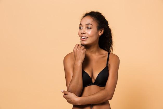 Ritratto di bellezza della donna sensuale che indossa lingerie nera, in piedi isolato sul muro beige