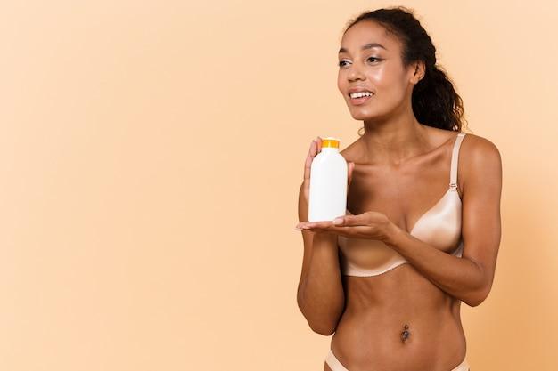 Ritratto di bellezza della donna sensuale che indossa lingerie bianca che tiene la bottiglia con cosmetici, mentre in piedi isolato sopra la parete beige