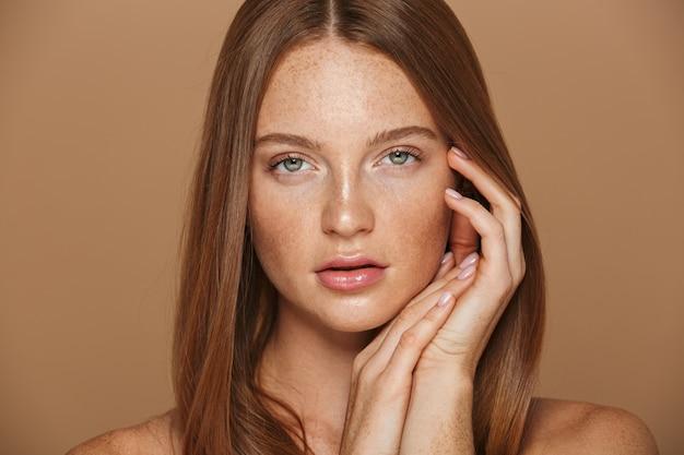 Ritratto di bellezza di una sensuale giovane donna in topless con lunghi capelli rossi in posa, tenendosi per mano sul viso isolato sopra il muro beige