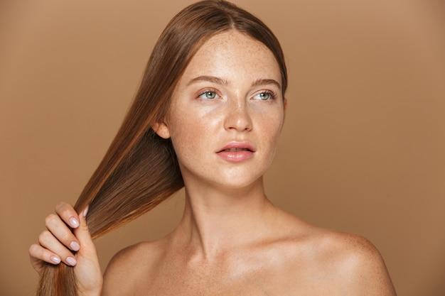 Ritratto di bellezza di una sensuale giovane donna in topless con lunghi capelli rossi in posa, giocando con i suoi capelli isolati sopra il muro beige