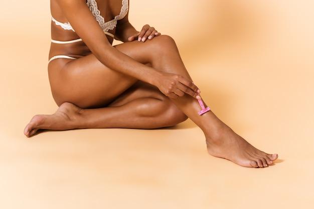 Ritratto di bellezza della donna magra che indossa lingerie bianca che rade le gambe, mentre era seduto sul pavimento isolato sopra il muro beige