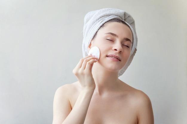 Il ritratto di bellezza della donna sorridente in asciugamano sulla testa con pelle sana molle che rimuove compone con il batuffolo di cotone isolato su fondo bianco. concetto di relax spa per la cura della pelle