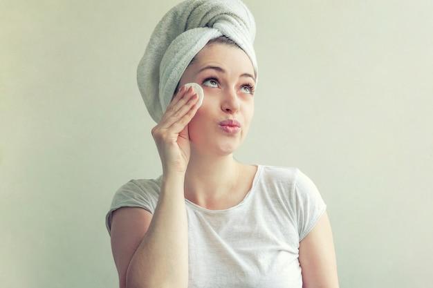 Il ritratto di bellezza della donna sorridente in asciugamano sulla testa con pelle sana molle che rimuove compone con il batuffolo di cotone isolato su fondo bianco. concetto di relax spa detergente per la cura della pelle