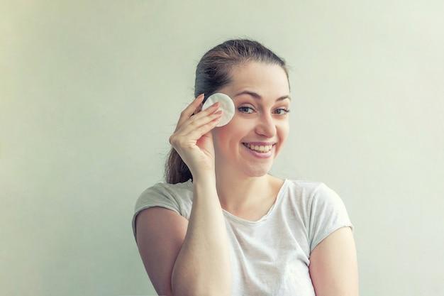 Ritratto di bellezza di donna sorridente con pelle morbida e sana che rimuove il trucco con un batuffolo di cotone isolato su sfondo bianco. concetto di relax spa detergente per la cura della pelle