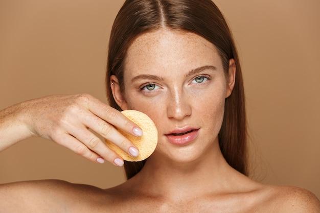 Ritratto di bellezza di una giovane donna sorridente in topless con lunghi capelli rossi che pulisce il viso con una spugna isolata sopra il muro beige