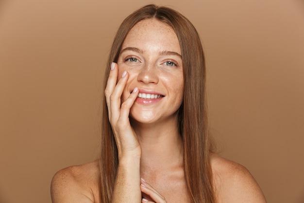 Ritratto di bellezza di una giovane donna sorridente in topless con lunghi capelli rossi in posa, tenendosi per mano sul viso isolato sopra il muro beige
