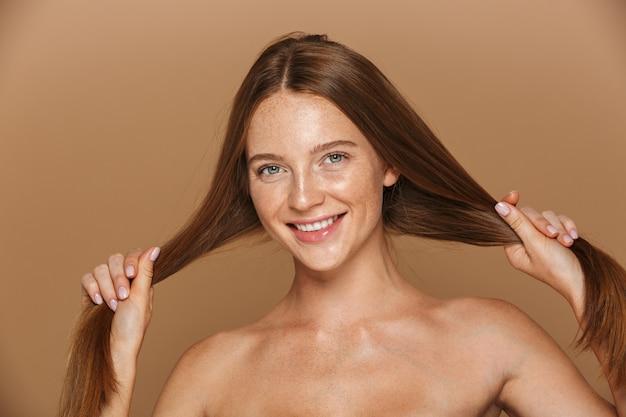 Ritratto di bellezza di una giovane donna sorridente in topless con lunghi capelli rossi in posa, giocando con i suoi capelli isolati sopra il muro beige