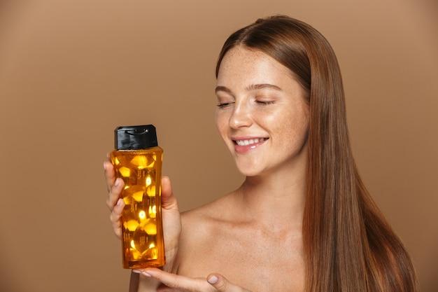 Ritratto di bellezza di una giovane donna sorridente in topless con lunghi capelli rossi che mostra una bottiglia di shampoo isolata sopra la parete beige