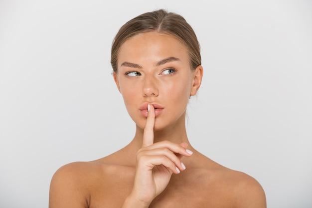 Ritratto di bellezza di una bella giovane donna in topless isolata, mostrando il gesto di pace, distogliendo lo sguardo