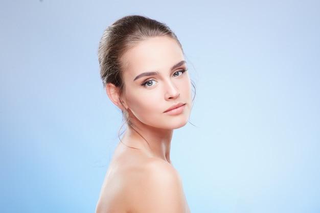 Ritratto di bellezza della donna che guarda l'obbiettivo, semi profilo. testa e spalle di donna tenera con trucco nudo, concetto di bellezza, primo piano, voltato da parte.