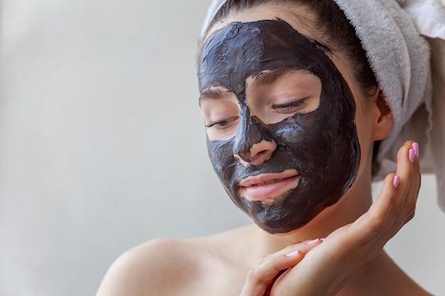 Ritratto di bellezza della donna in asciugamano sulla testa che applica la maschera nutriente nera sul fronte, fondo bianco isolato. cura della pelle pulizia eco cosmetica biologica spa relax concept