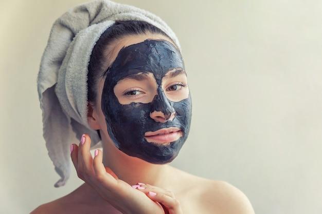 Ritratto di bellezza della donna in asciugamano sulla testa che applica la maschera nutriente nera sul fronte, fondo bianco isolato. cura della pelle pulizia eco cosmetici biologici spa relax concept