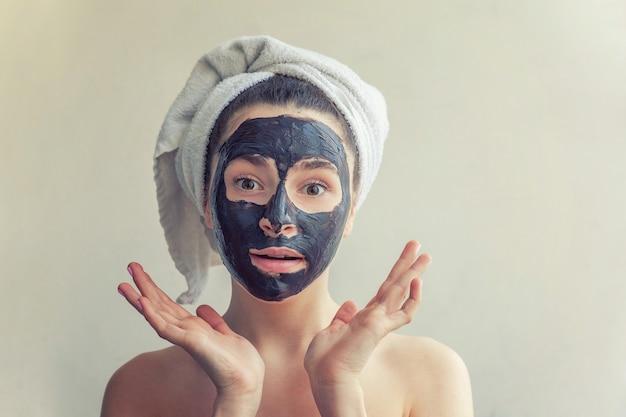 Ritratto di bellezza della donna in asciugamano sulla testa che applica maschera nutriente nera sul viso, sfondo bianco isolato