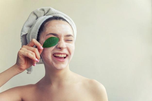 Ritratto di bellezza della donna in asciugamano sulla testa con maschera nutriente bianca o crema sul viso e foglia verde in mano, sfondo bianco isolato. concetto di spa cosmetica biologica ecologica detergente per la cura della pelle