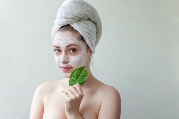 Ritratto di bellezza della donna in asciugamano sulla testa con maschera nutriente bianca o crema sul viso e foglia verde in mano, sfondo bianco isolato.