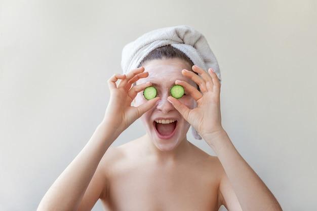 Ritratto di bellezza della donna in asciugamano sulla testa con maschera nutriente bianca o crema sul viso che tiene le fette di cetriolo, sfondo bianco isolato. cura della pelle pulizia eco cosmetica biologica spa relax concept
