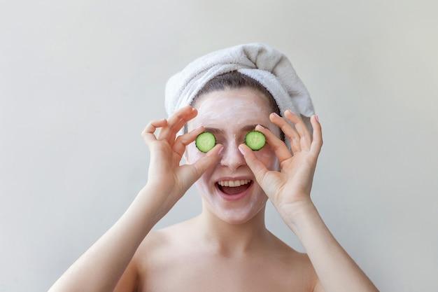 Ritratto di bellezza della donna in asciugamano sulla testa con maschera nutriente bianca o crema sul viso che tiene le fette di cetriolo