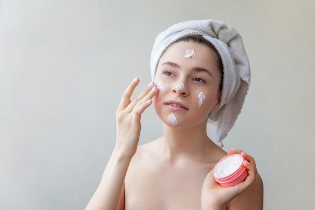 Ritratto di bellezza della donna in asciugamano sulla testa con maschera nutriente bianca o crema sul viso, sfondo bianco isolato. cura della pelle pulizia eco cosmetica biologica spa relax concept