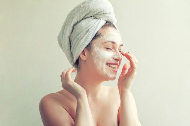Ritratto di bellezza della donna in asciugamano sulla testa con maschera nutriente bianca o crema sul viso, sfondo bianco isolato. cura della pelle pulizia eco cosmetici biologici spa relax concept