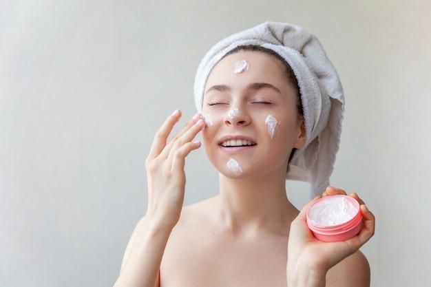 Ritratto di bellezza della donna in asciugamano sulla testa con maschera nutriente bianca o crema sul viso