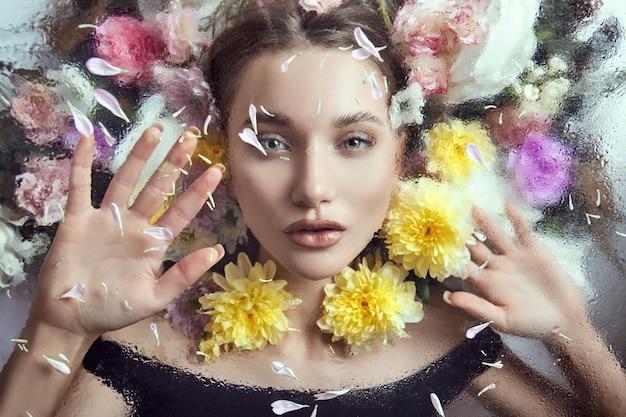 Ritratto di bellezza di una donna con fiori e petali dietro il vetro in gocce di pioggia