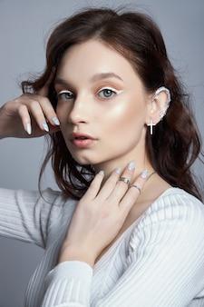 Ritratto di bellezza di una donna con trucco naturale e unghie lucidate dipinte sulla sua mano. anelli sulle dita della mano