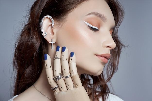 Ritratto di bellezza di una donna con trucco naturale e unghie lucidate dipinte sulla sua mano