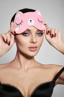 Ritratto di bellezza di una donna con una maschera per dormire e un trucco delicato rosa sulle labbra e sugli occhi. ragazza sexy del brunette in biancheria intima