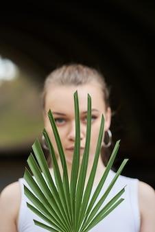 Ritratto di bellezza di una giovane donna bionda attraente in buona salute in piedi isolato più, tenendo il fiore vicino al suo viso