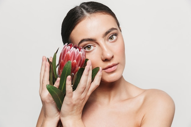 Ritratto di bellezza di una giovane donna castana attraente in buona salute in piedi isolato, tenendo il fiore sul viso