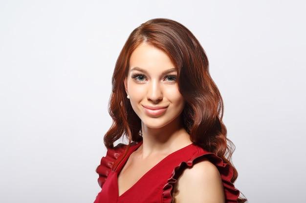 Ritratto di bellezza di una giovane donna dai capelli rossi su sfondo bianco.