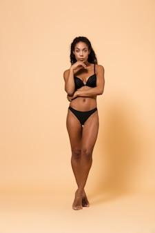 Ritratto di bellezza di giovane donna che indossa lingerie nera, in piedi isolato sul muro beige