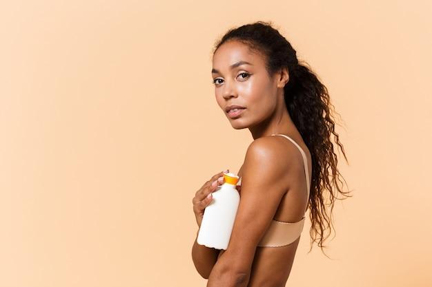 Ritratto di bellezza di giovane donna che indossa lingerie bianca che tiene la bottiglia con cosmetici, mentre in piedi isolato sul muro beige