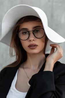 Ritratto di bellezza giovane donna con pelle pulita in occhiali vintage in giacca moda nera in cappello estivo elegante bianco paglia vicino alla parete grigia sulla strada. stile di eleganza.