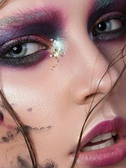 Ritratto di bellezza di una giovane donna con trucco creativo di moda. occhi fumosi colorati. sensualità, passione, concetto di trucco giovanile alla moda. primo piano estremo, vista parziale del viso