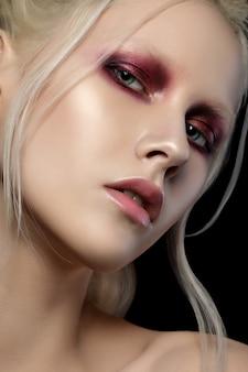 Ritratto di bellezza di giovane donna con capelli e sopracciglia bianche. pelle perfetta e trucco alla moda. occhi rossi smokey. sensualità, passione, concetto di trucco giovanile alla moda.