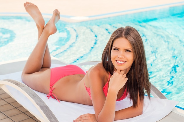 Bellezza rilassante in piscina. vista dall'alto di una bella giovane donna in bikini che tiene la mano sul mento e sorride mentre è sdraiata sulla sedia a sdraio a bordo piscina