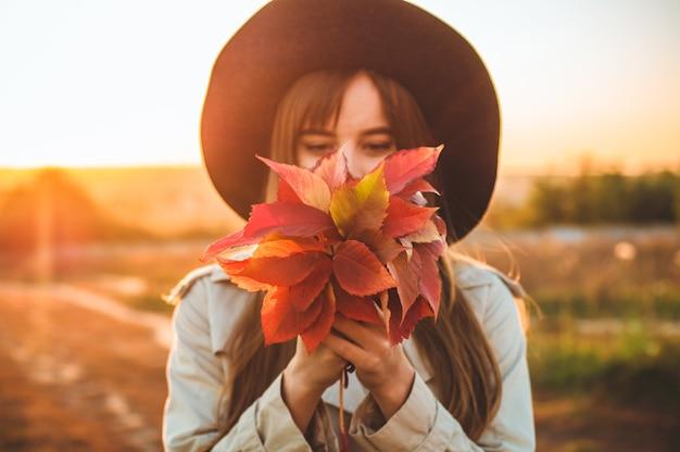 Bellezza donna romantica all'aperto che gode della natura che tiene le foglie nelle mani. bellissimo modello autunnale con agitando i capelli bagliore. luce del sole sul tramonto. ritratto di donna romantica